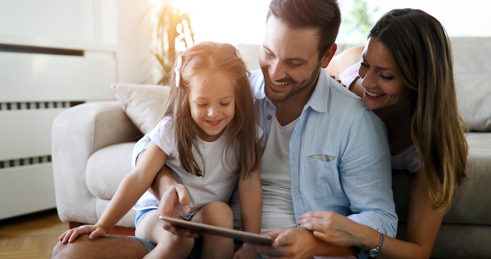 Must-download apps for families; Family holding a tablet and looking at it
