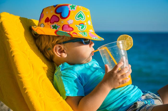 Summer bucket list; Boy kid in armchair with juice glass on beach against sea