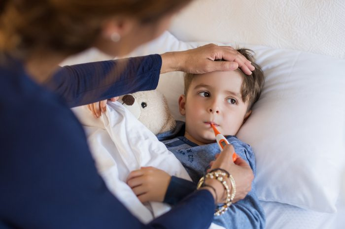 what to do when your child has a fever; Sick boy with thermometer laying in bed and mother hand taking temperature. Mother checking temperature of her sick son who has thermometer in his mouth. Sick child with fever and illness while resting in bed.