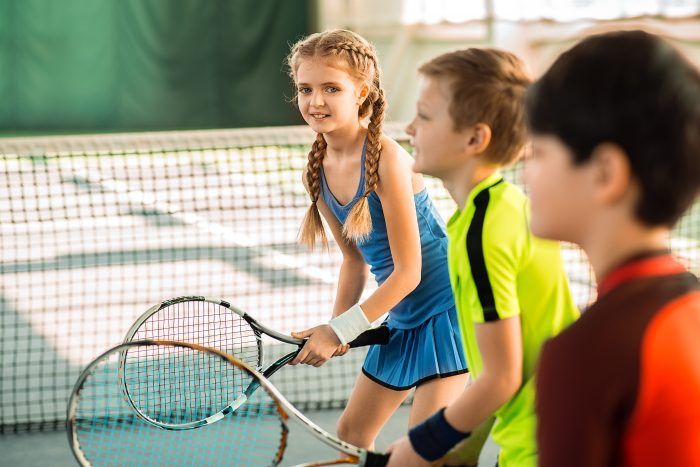 how to pick the best sport for your child; Portrait of carefree girl playing tennis with her friends. She is looking at camera and smiling