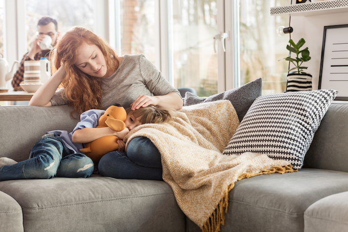 Mother taking care of her sleepy child while sitting on a couch in the living room; Blog: When to Keep Your Child Home from School