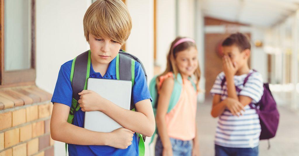 School friends bullying a sad boy in corridor; blog: signs of bullying