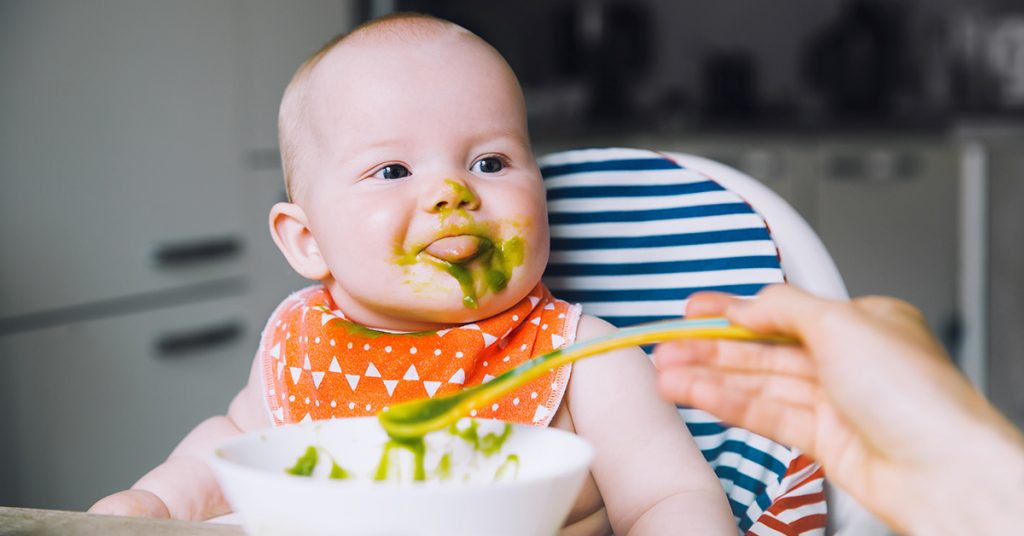 Feeding. Messy smiling baby eating with a spoon in high chair. Baby's first solid food. Mother feeding little child with spoon of puree. Daily routine. Finger food. Healthy child nutrition; blog: Baby's First Foods: Tips for Starting Solids