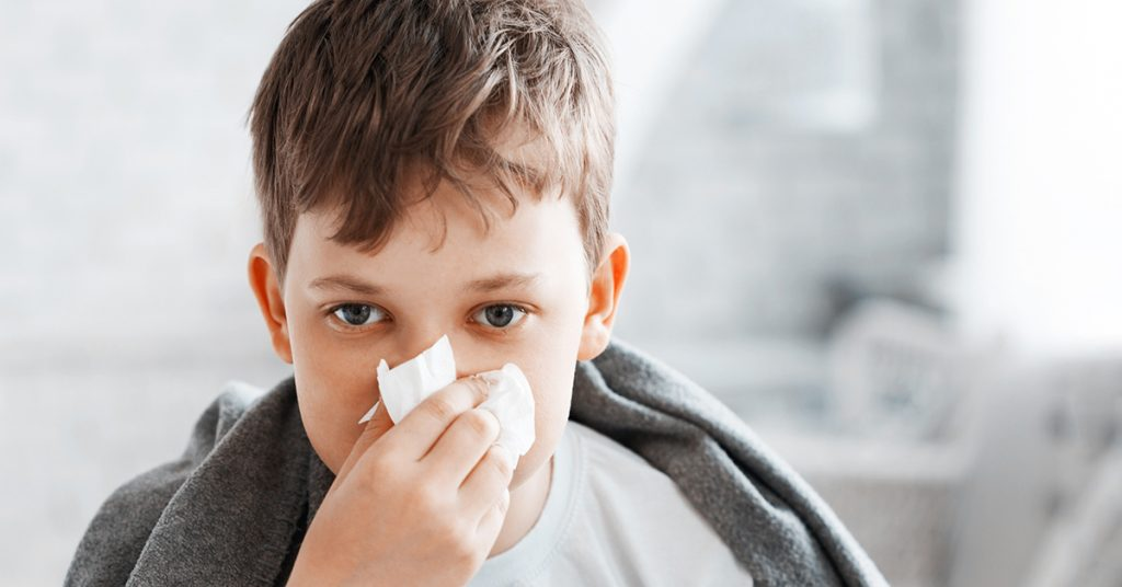 Boy get cold and blow her nose at home; blog: difference between cold and flu