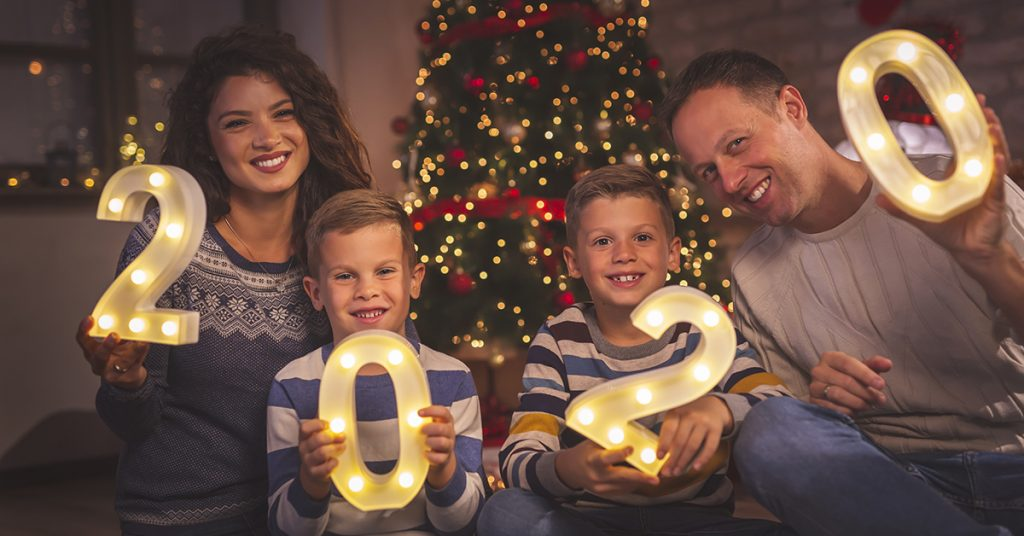 Parents celebrating New Years Eve at home with kids, sitting by the Christmas tree, holding illuminative numbers 2020 representing the upcoming New Year; blog: 9 New Year's Resolutions for the Whole Family