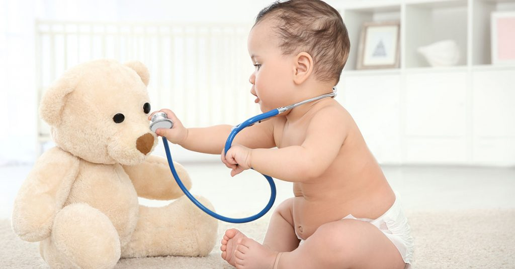 Cute little baby with stethoscope and toy bear playing at home. Health care concept; blog: tips for choosing a pediatrician