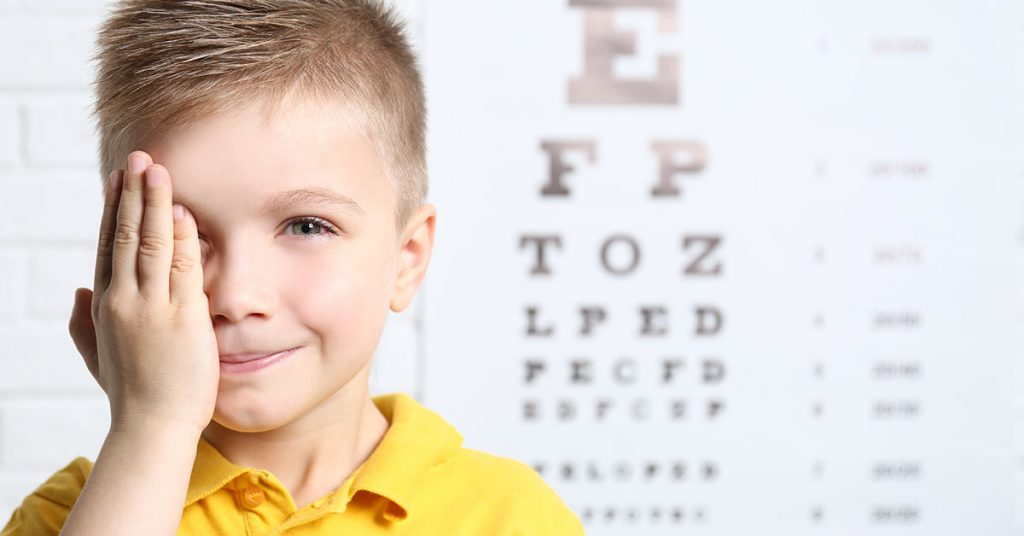 Little boy having eye test at ophthalmologist office; blog: eye tests for children: why screening is important