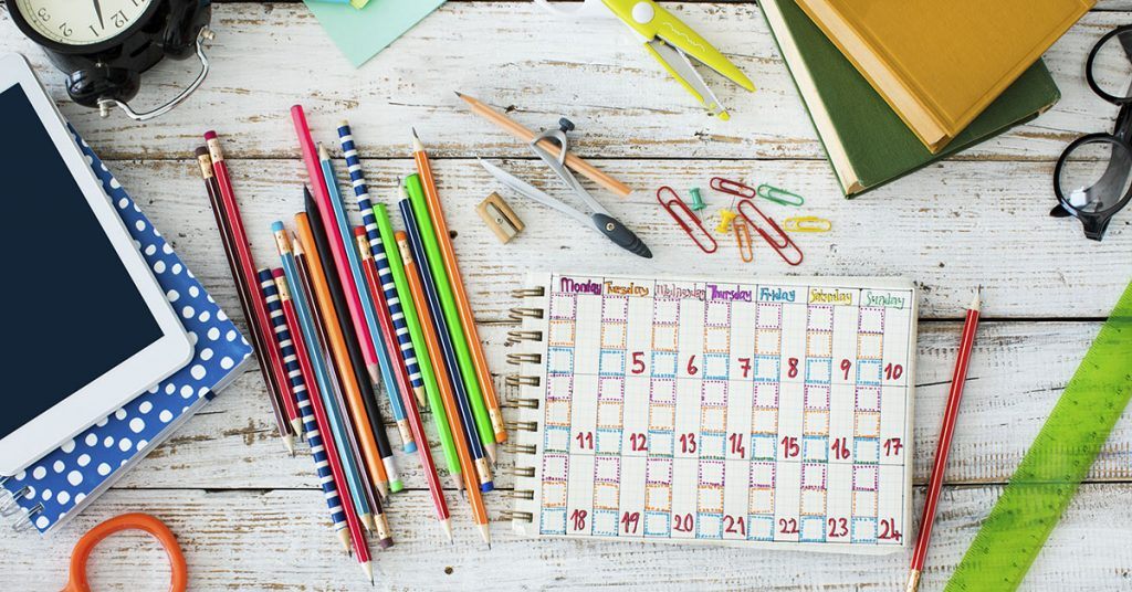 assortment of school supplies laid out on table; blog: 10 Tips for Making A Daily Schedule for Kids When School's Out