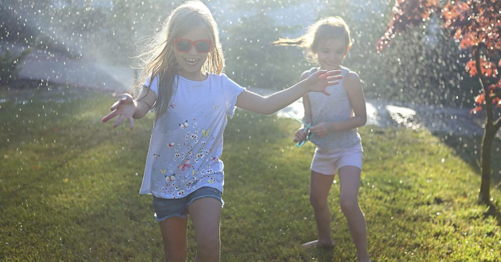 Child playing with garden sprinkler. Kids run and jump. Summer outdoor water fun in the backyard. Children play with hose watering flowers. Kids splash on sunny day; blog: 10 Fun Outdoor Activities for Kids This Summer