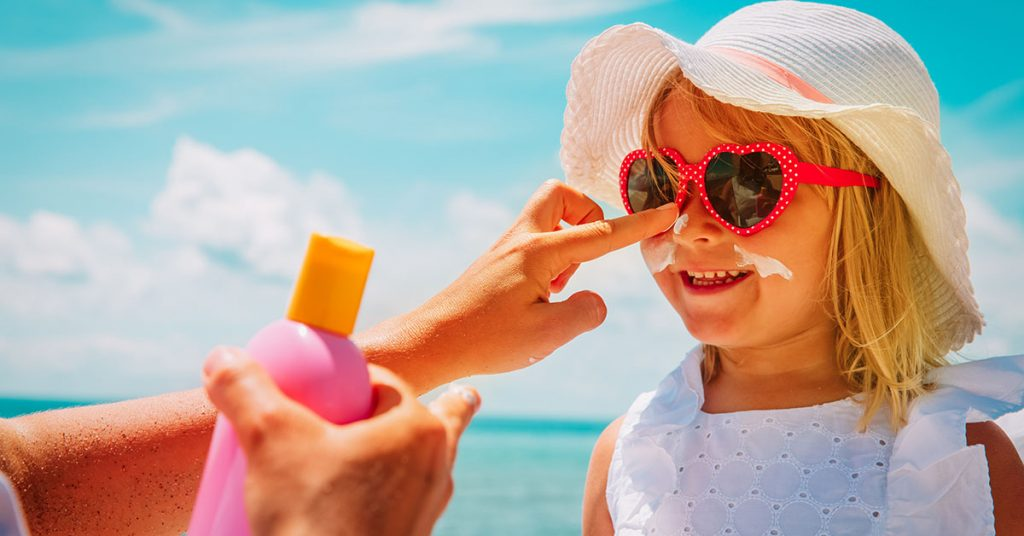 sun protection - mother put sunblock cream on little daughter face; blog: 6 Summer Safety Tips for Kids