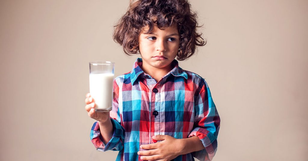 Kid boy with stomach pain holding a glass of milk. Dairy Intolerant person. Lactose intolerance, health care concept; blog: common food sensitivities in children