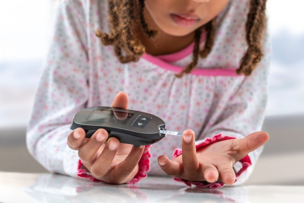 Concept children diabetes children with glucometer learning to check blood sugar level at home. Learn to use a glucometer. Education of diabetic kids, at hospital; blog: 6 Symptoms of Diabetes in Children