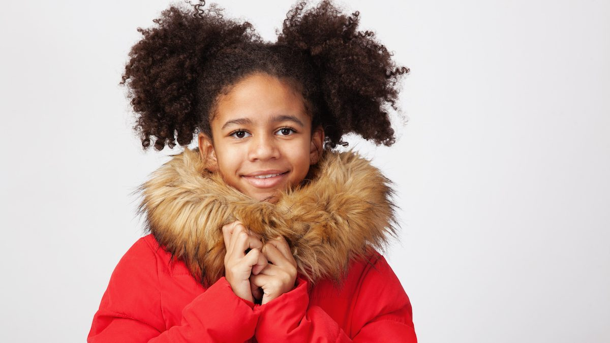 Cute teenage girl in red winter parka against white background; blog: Winter Safety Tips for Kids