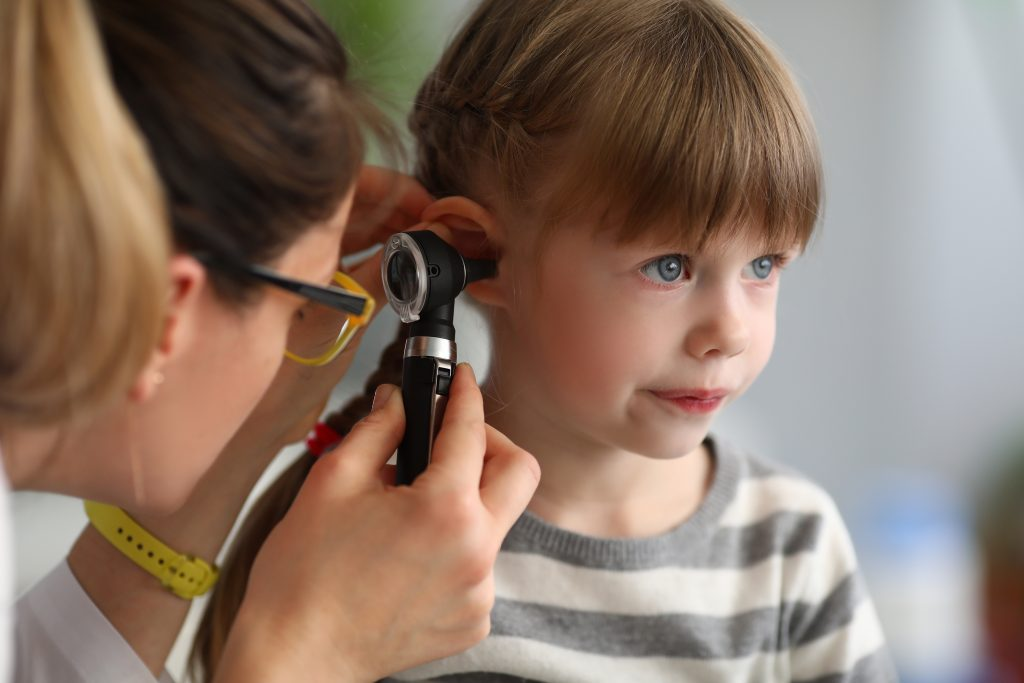 Pediatrician examines ear of sick child in office of hospital background; blog: Ear Nose and Throat Conditions Common in Kids